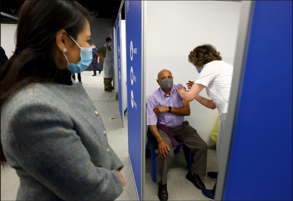 An image of Priti Patel watching a man receive a vaccination