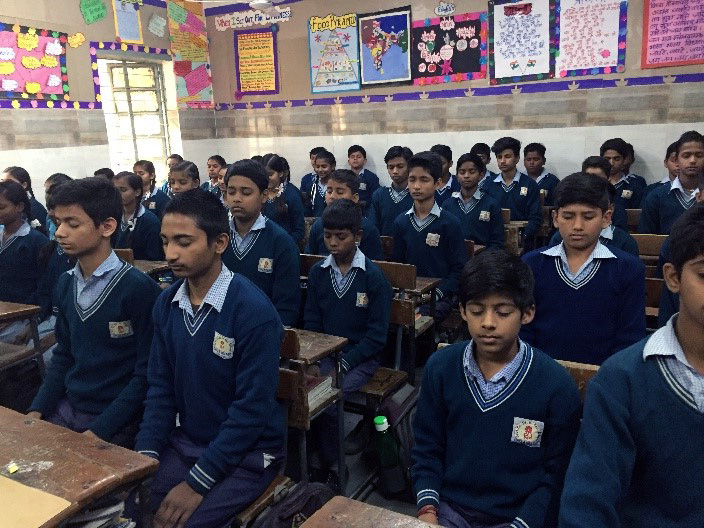 children sit at desks with eyes closed and hands in laps