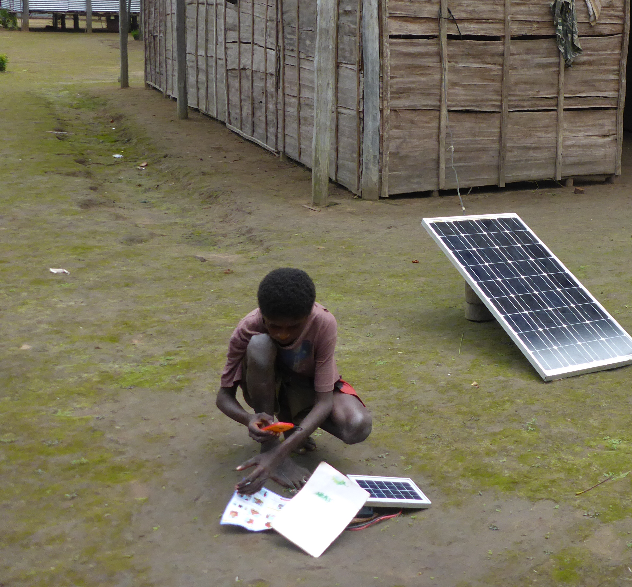 boy charging phone with solar power