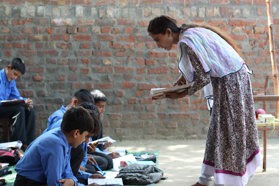 A teacher at a school in Kasur, Punjab stands over a class doing work