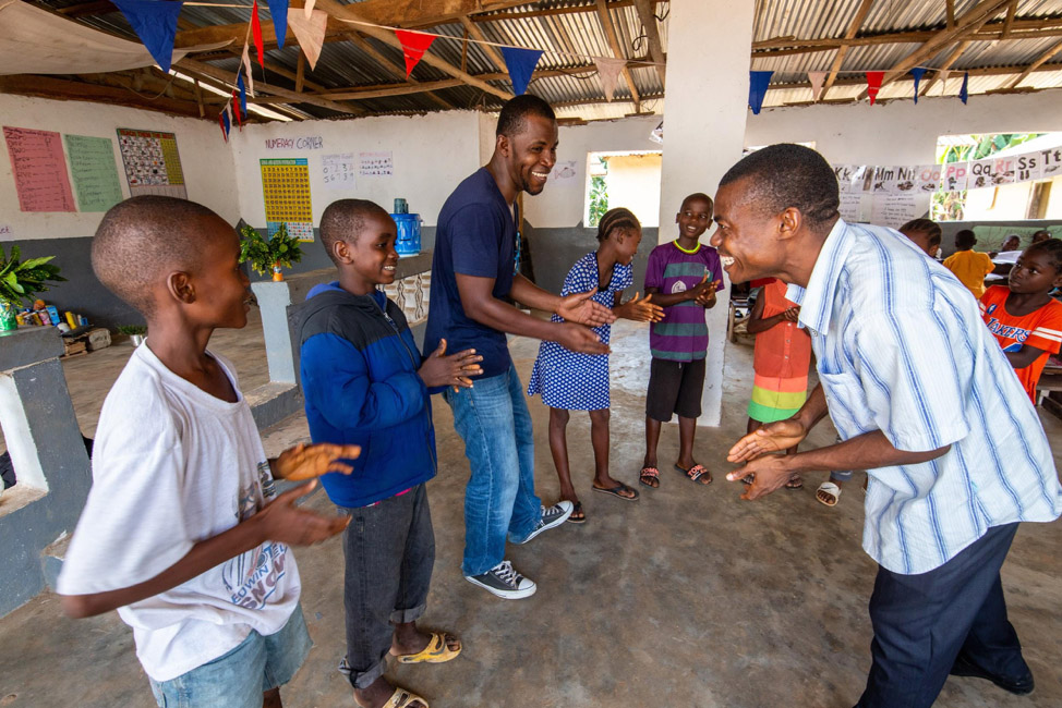 Two teachers lead students in a game at a school in Liberia