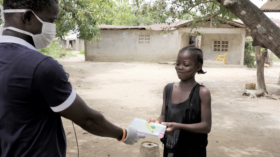 A student in Liberia receives her learning material to continue studying at home