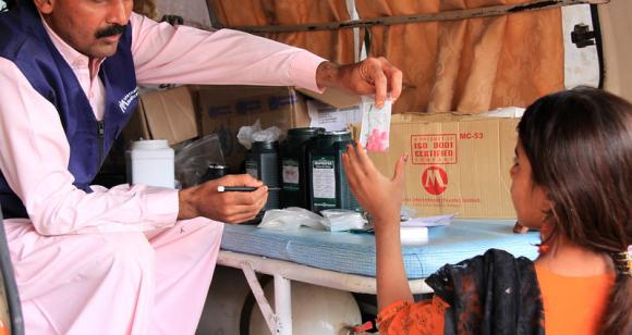 A pharmacist in an International Medical Corps mobile health clinic dispenses medicine to a sick child in a remote village in Pakistan's Sindh province.
