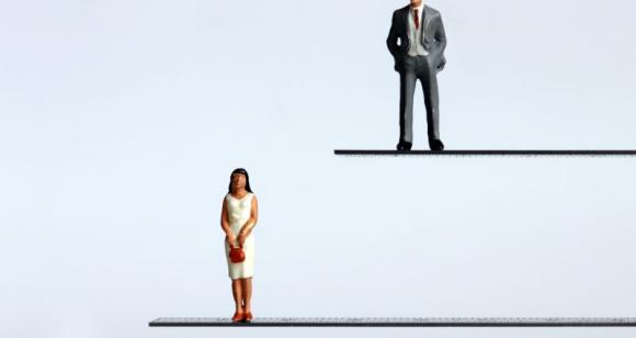 A miniature man and a miniature woman standing at different heights.