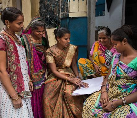 women in India discuss a document
