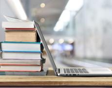 An image of books and a laptop on a desk.