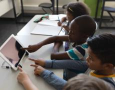An image of school children learning on a tablet.