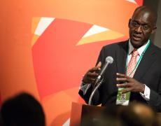 Makhtar Diop speaks into a microphone in front of an orange backdrop