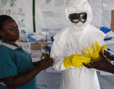 A health worker suits up in Liberia during the Ebola epidemic. Photo by Martine Perret / UNMEER