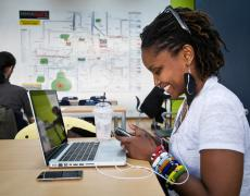A woman smiles at her phone while working at her laptop at iHub, a coworking space in Kenya