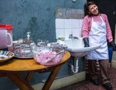 A Peruvian woman smiles in her kitchen, wearing dish washing gloves