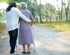 An elderly woman with a walker, being helped by someone else