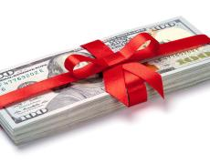 A pile of money, giftwrapped. Adobe Stock.