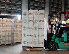 A forklift moves pallets of USAID supplies. Photo by Lance Cheung/USDA.