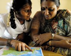Haritha, a pupil, and her mother look at a map of England in a Chennai classroom.