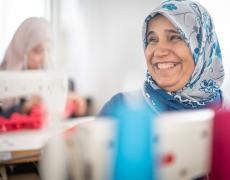 Halima, a Syrian refugee enrolled in the cash-for-work tailoring program, smiles while sewing at  Azraq refugee camp in Jordan