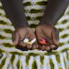 A girl holds a handful of pills